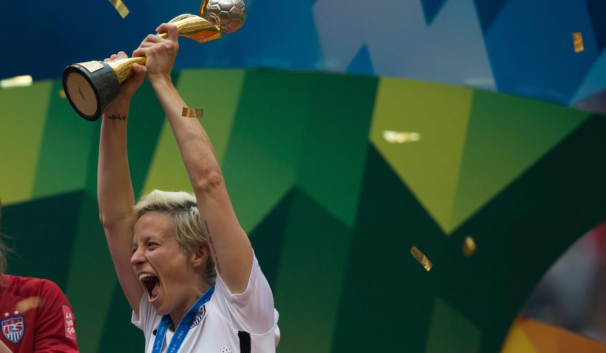 United States' Megan Rapinoe hoists the trophy as she celebrates after defeating Japan to win the FIFA Women's World Cup soccer championship in Vancouver, British Columbia, Canada, on July 5, 2015. (Darryl Dyck/The Canadian Press via Associated Press)