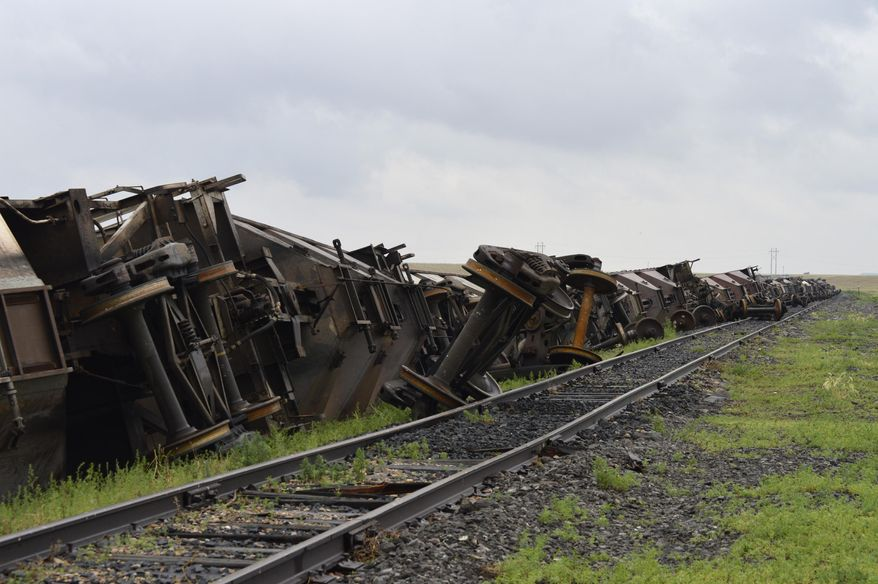 In this Sunday, July 5, 2015, photo, more than 10 empty BNSF Railway cars lie on the ground after they were blown on their sides south of Havre, Mont., during a strong storm that moved across the northern part of Montana on Saturday. Straight-line winds blew at speeds of up to 90 mph and hail as large as ping pong balls fell on Saturday night, uprooting trees, flattening crops, damaging buildings and breaking windows, the National Weather Service said. (Amber Wells/Havre Daily News via AP) MANDATORY CREDIT