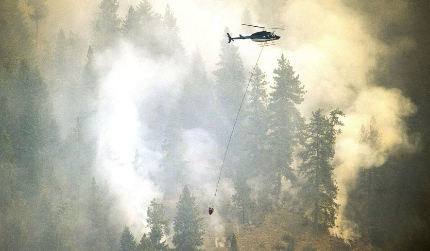 A helicopter carries water to douse the fire that is burning above Bayview, Idaho, Monday, July 6, 2015. The wildfire in northern Idaho has destroyed several homes and forced about hundreds of residents in an upscale lakeside community to evacuate as it ballooned to more than 3 square miles Monday. (Kathy Plonka/The Spokesman-Review, via AP) MANDATORY CREDIT