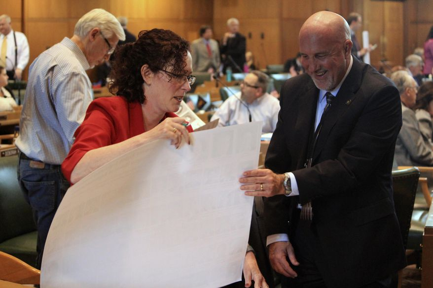 Rep. Val Hoyle, D-Eugene, and Rep. Bill Post, R-Keizer, sign posters for their legislative colleagues on Monday, July 6, 2015 at the state Capitol in Salem, Ore. Lawmakers pushed Monday to adjourn the 2015 legislative session. (AP Photo/Jonathan J. Cooper)