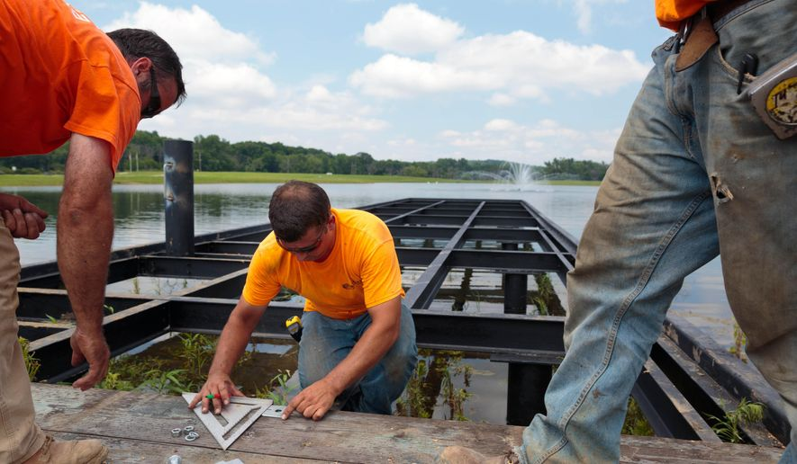 In this Wednesday, July 1, 2015 photo, Bob Blake, from left, John Schmitt and Jake Reid work to put down planks on the pier at American Heroes Park in Bellevue, Neb. (Matt Miller/The World-Herald via AP)