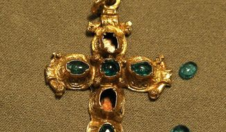 In this Thursday, June 18, 2015 photo, a gold crucifix with inlaid Colombian emerald jewels sits on display in New York. The crucifix was one of many pieces of jewelry pulled from the 400-year-old wreckage of the Nuestra Senora de Atocha Spanish galleon and will be one of forty select items auctioned off by Guernsey's next month. (AP Photo/Julie Jacobson)