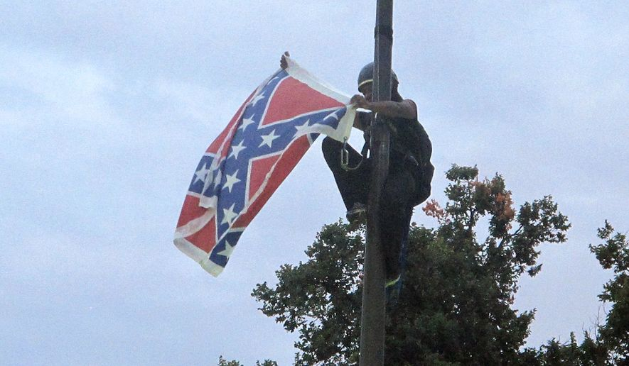 Bree Newsome of Charlotte, N.C., removes the Confederate battle flag at a Confederate monument at the Statehouse in Columbia, S.C., on Saturday, June, 27, 2015. She was taken into custody when she came down. The flag was raised again by capitol workers about 45 minutes later. (Associated Press)