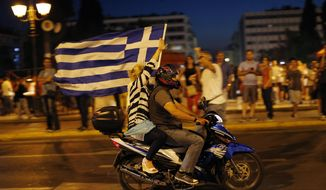 A supporter of the No vote waves a Greek flag after the first results of the referendum at Syntagma square in Athens, Sunday, July 5, 2015. (AP Photo/Emilio Morenatti)
