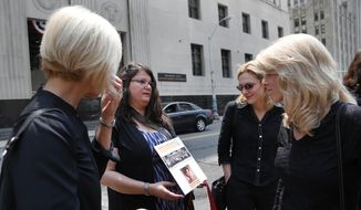 Liz Lupo, second from left, shows a sign in honor of her mother, Marianne Lupo, a former patient of Dr. Farid Fata, outside federal court, Monday, July 6, 2015, in Detroit. (AP Photo/Paul Sancya)