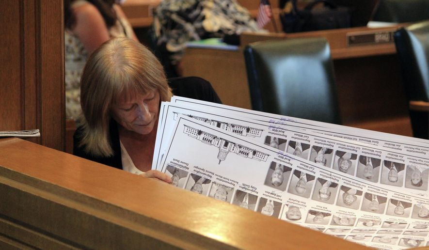 Rep. Susan McLain, D-Forest Grove, signs below her photo on posters for her legislative colleagues on Monday, July 6, 2015, at the state Capitol in Salem, Ore. Lawmakers pushed Monday to adjourn the 2015 legislative session. (AP Photo/Jonathan J. Cooper)