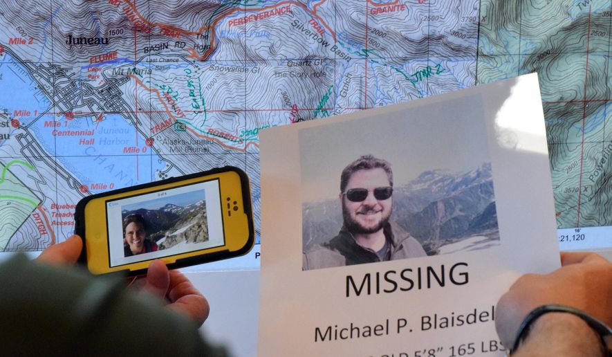 In this July 5, 2015 photo, a searcher uses a personal selfie, left, in the Timberline Bar and Grill on Mount Roberts to establish the location where Michael Patrick Blaisdell took his final photograph the day before in Juneau, Alaska. Alaska State Troopers say the body of Blaisdell of Orlando, Fla., was found Sunday night near the base of an about 50-foot drop in Bear Valley, east of downtown Juneau. (James Brooks/The Juneau Empire via AP)