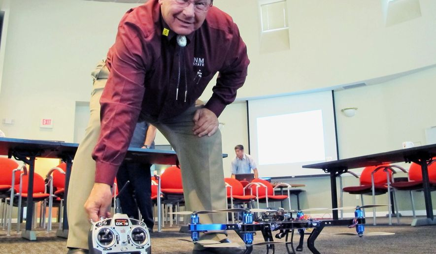Dennis Zaklan, deputy director of New Mexico State University's Unmanned Aircraft Systems Flight Test Center, poses for a photo with one of the controls for one of the university's drones following a legislative committee meeting in Albuquerque, N.M., Monday, July 6, 2015. Lawmakers heard from a panel of witnesses about the benefits of the technology as well as privacy concerns. (AP Photo/Susan Montoya Bryan)