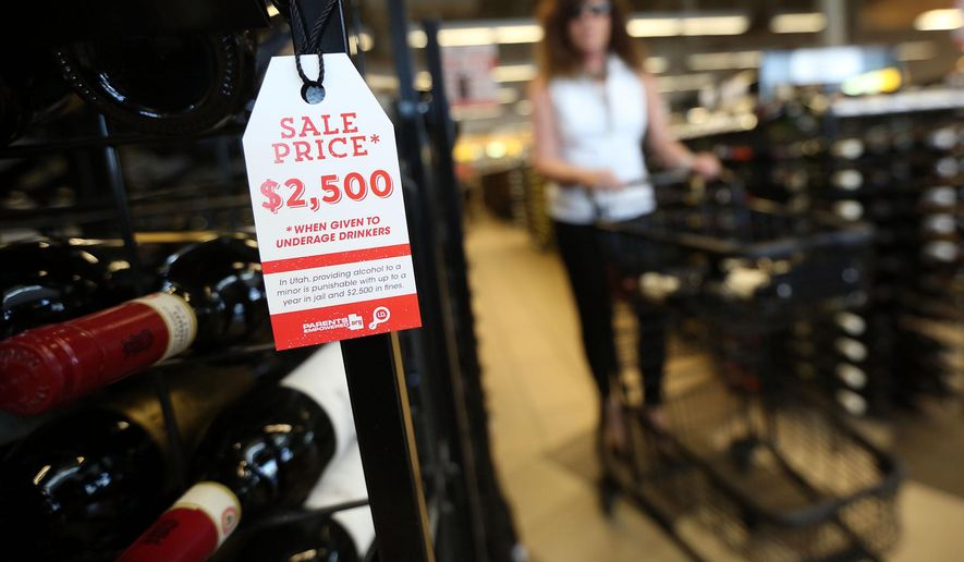 In this Thursday, July 2, 2015 photo, a shopper passes an informational tag at the Utah State Liquor Store in Holladay, Utah. Liquor bottles will bear sale tags in Utah this summer that remind adults that giving alcohol to minors can mean a possible $2,500 fine and up to a year in jail. (Kristin Murphy/The Deseret News via AP)