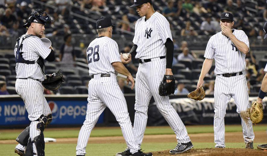 New York Yankees pitcher Dellin Betances hands the ball to manager Joe Girardi (28) as catcher Brian McCann, left, and third baseman Chase Headley react as Betances leaves the game after giving up a home run in the 10th inning of a baseball game against the Oakland Athletics Tuesday, July 7, 2015, at Yankee Stadium in New York. The Athletics defeated the Yankees 4-3. (AP Photo/Bill Kostroun)
