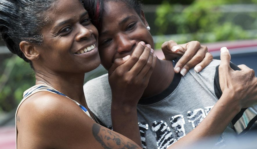 In this Monday, July 6, 2015 photo, Jessica Byrd, right, reacts with her mother Hattie Byrd after seeing a rendering of the home being built for her during a groundbreaking ceremony in Montgomery, Ala. Jessica Byrd's former home occupied the same space before it caught fire, killing two of her three children. (Mickey Welsh/The Montgomery Advertiser via AP)
