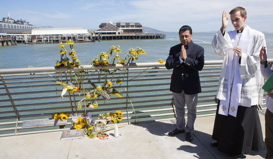Father Cameron Faller, right, and Julio Escobar, of Restorative Justice Ministry, conduct a vigil for Kathryn Steinle, Monday, July 6, 2015, on Pier 14 in San Francisco.  (AP Photo/Beck Diefenbach)
