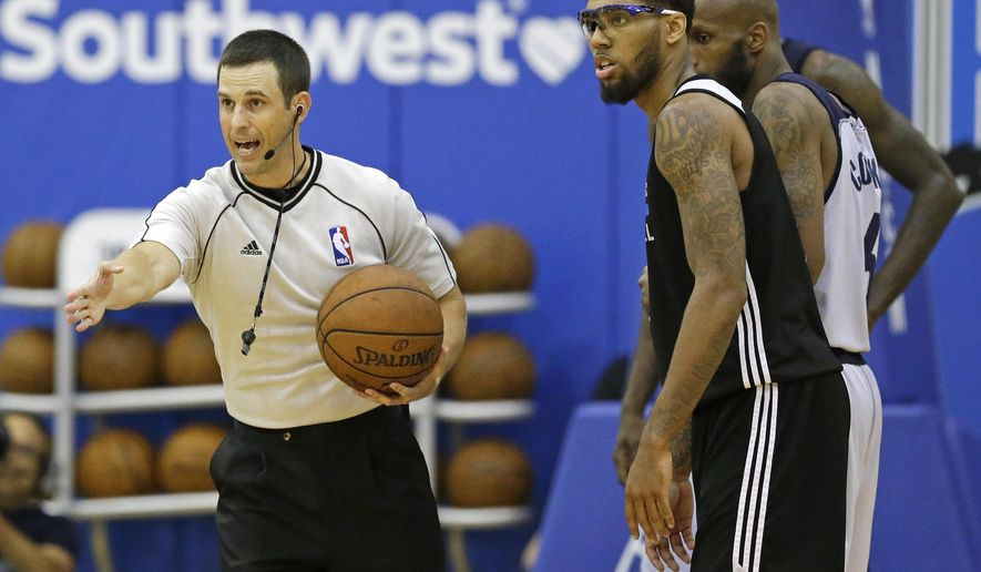 Referee Kevin Scott, left, officiates next to Orlando Magic Blue's Devyn Marble during the second half of an NBA summer league basketball game between Orlando and the Memphis Grizzlies , Tuesday, July 7, 2015, in Orlando, Fla. (AP Photo/John Raoux)