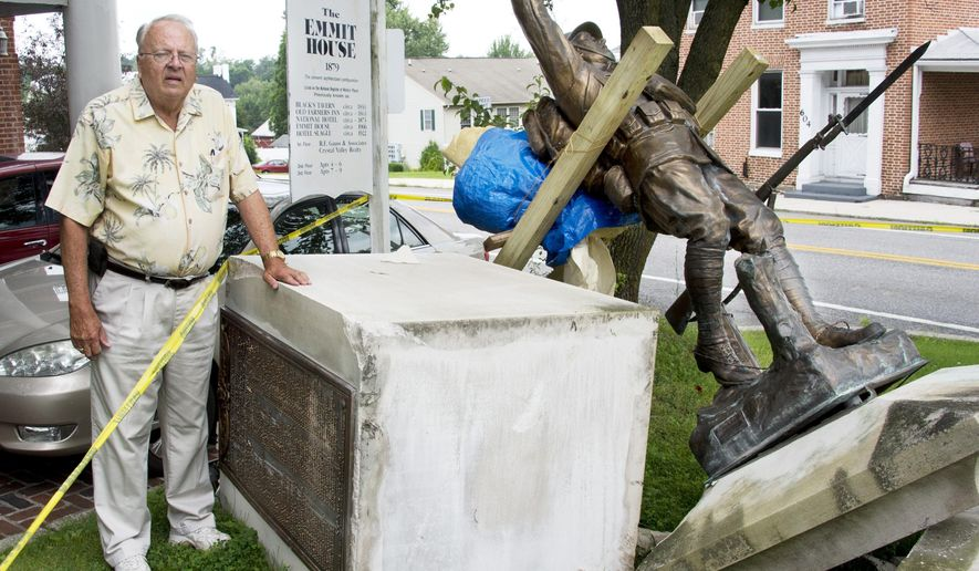 In this Monday, July 6, 2015 photo, resident Bob Rosensteel stands next to the Emmitsburg World War I Memorial, which was recently damaged after being hit by a vehicle, in Emmitsburg, Md. Rosensteel is leading the effort to redo the plaque on the memorial to combine the lists of white and black veterans. (Sam Yu/The Frederick News-Post via AP)