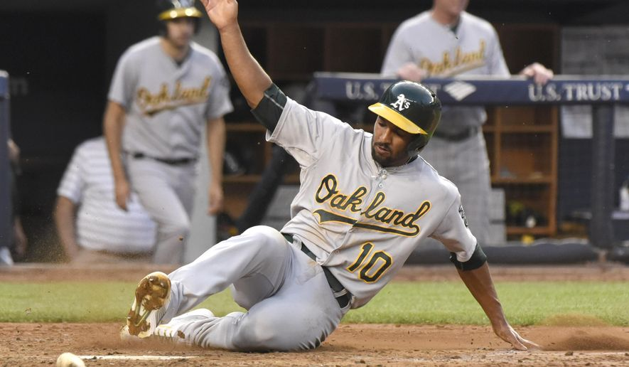Oakland Athletics' Marcus Semien scores on a single by Stephen Vogt during the third inning of a baseball game against the New York Yankees Tuesday, July 7, 2015, at Yankee Stadium in New York. (AP Photo/Bill Kostroun)
