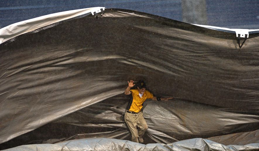 Pittsburgh Pirates grounds crew member Jeff Miller tries to control the tarp on the infield Tuesday night, July 7, 2015, as a storm blows into PNC Park during a baseball game between the Pirates and the San Diego Padres in Pittsburgh. (Matt Freed/Pittsburgh Post-Gazette via AP) MAGS OUT; NO SALES; MONESSEN OUT; KITTANNING OUT; CONNELLSVILLE OUT; GREENSBURG OUT; TARENTUM OUT; NORTH HILLS NEWS RECORD OUT; BUTLER OUT