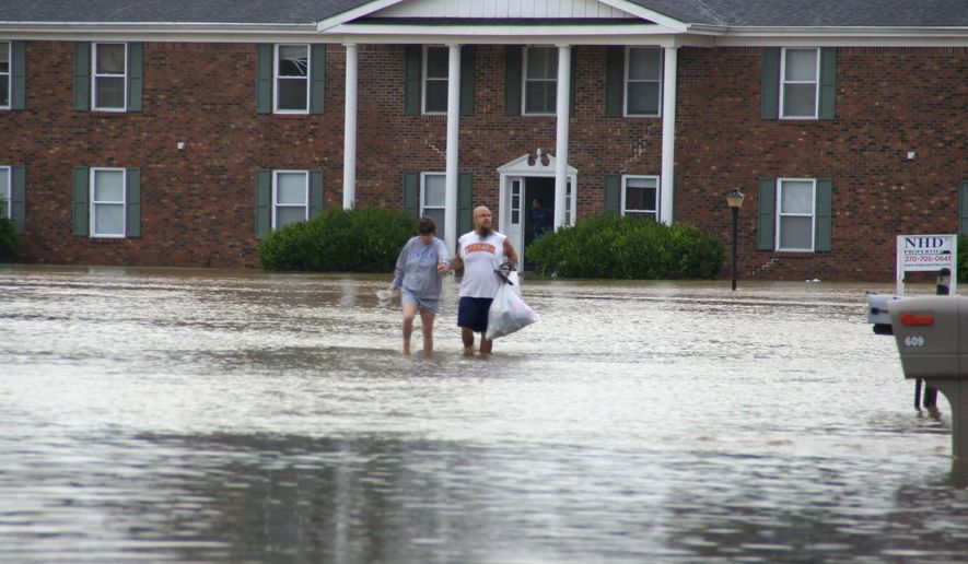 A couple wades through floodwaters in Paducah, Ky., Tuesday, July 7, 2015.  Heavy rain in part of western Kentucky has led to multiple water rescues including at an apartment complex that was evacuated. The National Weather Service said radar showed that 3 to 5 inches of rain fell Tuesday morning in areas of McCracken, Ballard, Marshall and Livingston counties. (Gary Goin West Kentucky Star (WKYX) via AP)