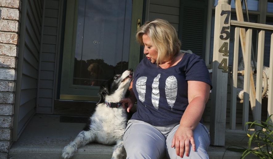 In this Thursday, July 2, 2015 photo, Becky Rehr pets her dog, Dexter, in Cooper Township, Mich. Rehr says she's no longer facing a misdemeanor charge after being arrested for failing to renew her dog's license. (Crystal Vander Weit/Kalamazoo Gazette-MLive Media Group via AP)