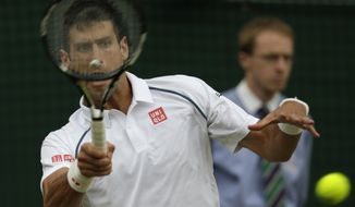 Novak Djokovic of Serbia returns a ball to Kevin Anderson of South Africa during their singles match against at the All England Lawn Tennis Championships in Wimbledon, London, Tuesday July 7, 2015. (AP Photo/Alastair Grant)