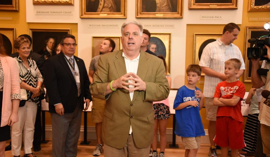 In this Monday, July 6, 2015 photo provided by the Executive Office of the Governor of the state of Maryland, Gov. Larry Hogan speaks during an unscheduled appearance at the restored Old Senate Chamber, in Annapolis, Md. It was Hogan's first public appearance since finishing his opening round of chemotherapy a week earlier for treatment of non-Hodgkin's lymphoma. The chamber was closed for three years while undergoing $8 million in restoration. (Joe Andrucyk/Executive Office of the Governor via AP)