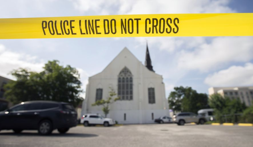 Police tape surrounds the parking lot behind the AME Emanuel Church on June 19 as FBI forensic experts work the crime scene where nine people where shot by Dylann Storm Roof, 21, in Charleston, S.C. (Associated Press)