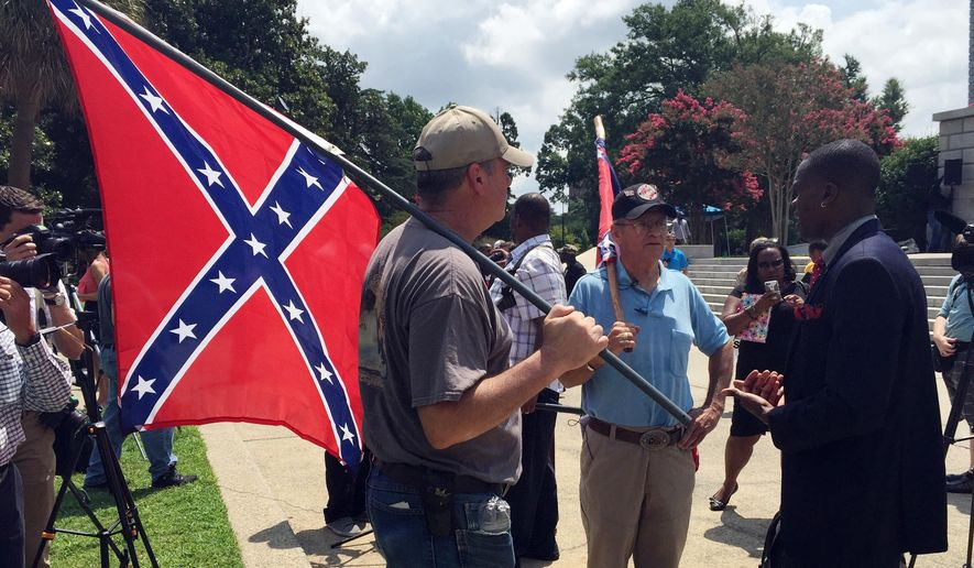 Randy Saxon, left and Wayne Whitfield, both of Anderson, S.C., discuss the Confederate flag on the South Carolina Statehouse grounds with Brodrick S. Hall of Atlanta, right, on Monday, July 6, 2015. Lively discussions on the flag took place on the grounds took place outside the state house where lawmakers debated whether the flag should be removed from the downtown Columbia complex.  ( AP Photo/ Meg Kinnard)