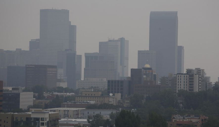 Smoke drifting south from wildfires burning in Canada clouds the skyline Tuesday, July 7, 2015, in Denver. A smoke advisory was issued for the northeastern part of Colorado, Monday and expanded to all counties east of the Continental Divide Tuesday. (AP Photo/David Zalubowski)