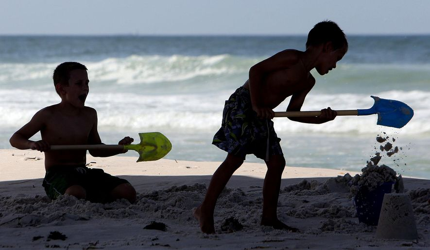 FILE - In this Monday, June 15, 2015, file photo, kids build a sand castle beneath the M.B. Miller County Pier in Panama City Beach, Fla. Panama City Beach is having a record-breaking summer tourism season. Experts say local officials have done a good job of addressing the spring beak mayhem by passing regulations designed to curtail beach drinking and unruly crowds during future spring breaks. (Andrew Wardlow/The News Herald via AP, File)