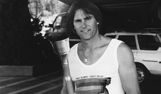 In this 1984 photo provided by Heritage Auctions, American Decathlete, Bruce Jenner poses with the 1984 Olympic Torch he carried through Lake Tahoe, Nevada. The 24-inch torch, featuring a brass finish and wood handle, is being offered by Heritage Auctions on July 30, 2015 at its Platinum Night Sports Auction in Chicago. It is the first significant piece of Jenner memorabilia to go to auction since the winner of the 1976 Olympic Decathlon Gold Medal became Caitlyn Jenner. (Heritage Auctions via AP)