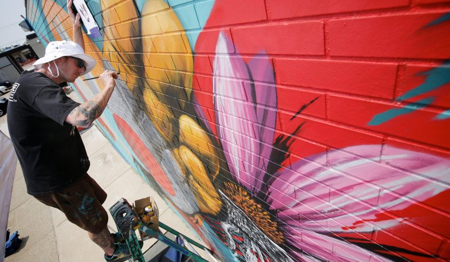 """In this photo taken on Monday, July 6, 2015, Australian born Los Angeles based artist Meggs works on a new mural north of Shedd 5 in Detroit's Eastern Market. The mural will be unveiled Tuesday as part of a weeklong festival beginning in September titled """"Murals In The Market""""  and will feature the work of more than 45 local and international artists who will paint large scale murals throughout Eastern Market. (Salwan Georges /Detroit Free Press via AP)  DETROIT NEWS OUT; TV OUT; MAGS OUT; NO SALES; MANDATORY CREDIT DETROIT FREE PRESS"""