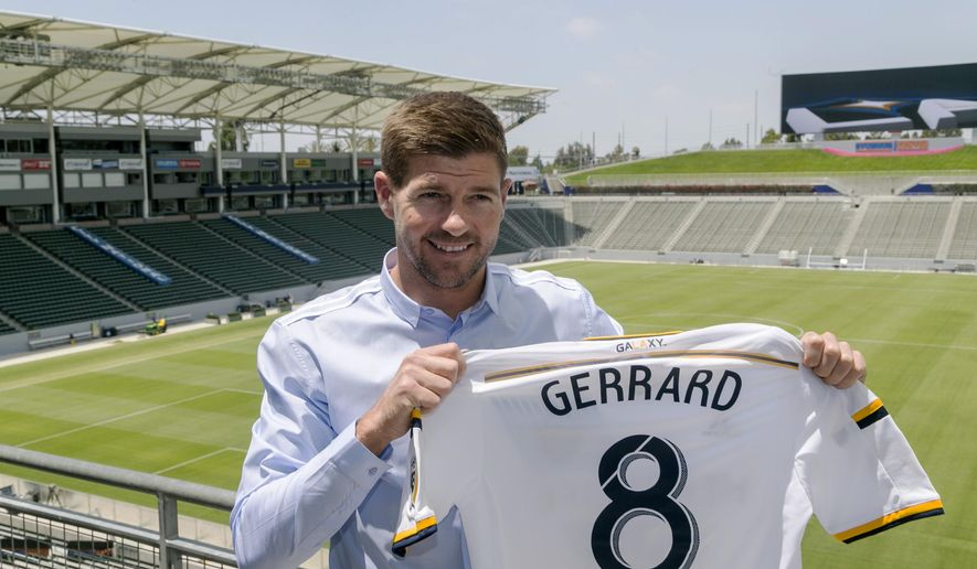 Los Angeles Galaxy new midfielder, Steven Gerrard poses with his new team's  jersey after a news conference at StubHub Center in Carson, Calif., on Tuesday, July 7, 2015. The former England captain could play this weekend for the defending MLS champions. (AP Photo/Damian Dovarganes)
