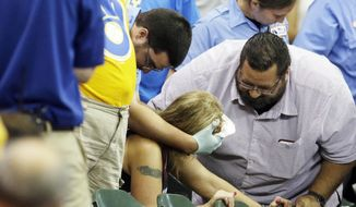In this Monday, July 6, 2015, photo, a fan is helped after being hit by a foul ball during the ninth inning of a baseball game between the Milwaukee Brewers and the Atlanta Braves in Milwaukee. (AP Photo/Morry Gash)