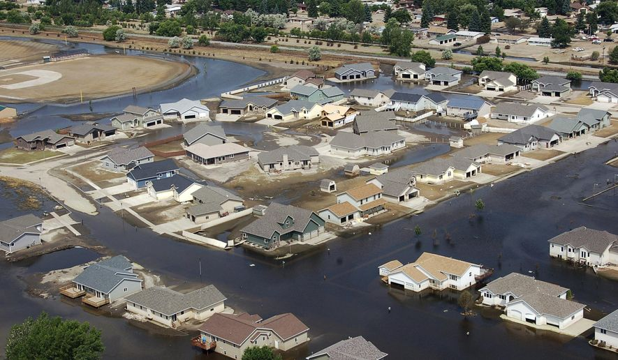 FILE - In this July 13, 2011 file photo, homes flooded by the Souris River are shown in Minot, N.D. North Dakota officials are pushing the Army Corps of Engineers to make long-term flood protection for the Souris River Valley a priority. Local and state officials fear that any work they do on a proposed $1 billion protection plan might mitigate the flood threat enough that federal officials will decide they don't need to get involved. (AP Photo/James MacPherson, File)