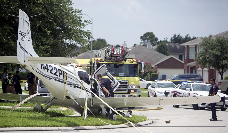 Authorities investigate after a plane made an emergency landing along Laurel Bank Way in North West Houston, Tuesday, July 7, 2015. Authorities say the pilot of the small plane reported engine trouble and deployed an emergency chute before landing in the Houston-area neighborhood. Authorities say the pilot and a passenger were being treated for minor injuries.  (Cody Duty/Houston Chronicle via AP)