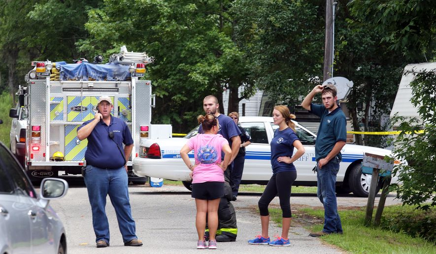 Emergency personnel from Berkeley County stand outside a campground surrounded by police tape near Moncks Corner, S.C., Tuesday, July 7, 2015, after an F-16 fighter jet smashed into a small plane over South Carolina. (Brad Nettles/The Post and Courier via AP) MANDATORY CREDIT