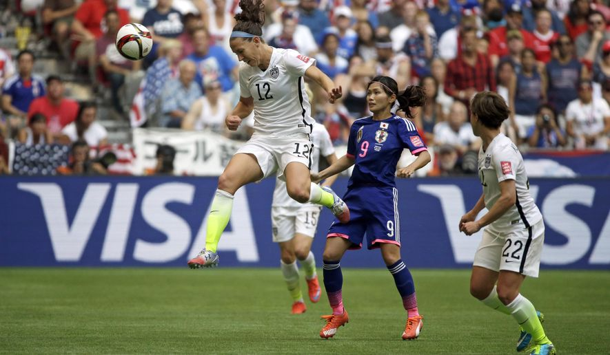 United States' Lauren Holiday (12) heads the ball above Japan's Nahomi Kawasumi (9) during the first half of the FIFA Women's World Cup soccer championship in Vancouver, British Columbia, Canada, Sunday, July 5, 2015. (AP Photo/Elaine Thompson)