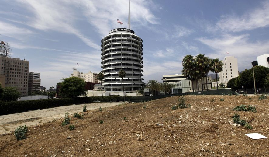 FILE - This Friday, Aug. 3, 2013 file photo shows the Capitol Records building beyond the site of the Millennium Hollywood development in the Hollywood district of Los Angeles. Los Angeles building officials on Monday, July 6, 2015 approved plans to build the 1 million-square-foot complex of skyscrapers, stores and restaurants on the lot, agreeing with the developer that an earthquake fault underneath the property is too old to be considered active. (AP Photo/Reed Saxon, File)