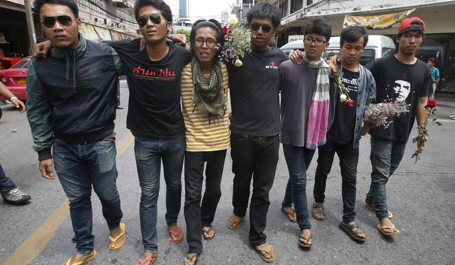 In this June 24, 2015 photo, student activists gather outside Pathumwan Police Station in Bangkok, Thailand. Fourteen detained student activists went before a military court in Thailand on Tuesday, July 7, 2015 in a case that has attracted international calls for their release and criticism of the military junta's strict controls on freedom of speech and assembly. The university students, 13 men and one woman, were arrested June 26 on charges of sedition and violating the junta's ban on political gatherings for leading a peaceful anti-coup rally in Bangkok. (AP Photo/Sakchai Lalit)