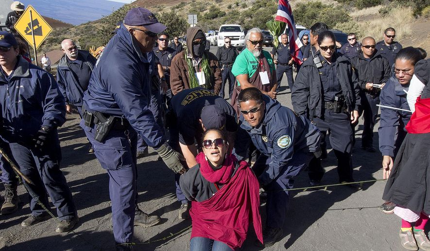 FILE - In this April 2, 2015, file photo, Department of Land and Natural Resources officers arrest a protester on the road to Thirty Meter Telescope building site on the summit of Mauna Kea in Hilo, Hawaii. Instead of a trial, most of the people arrested in April for blocking construction of a giant mountaintop telescope will likely participate in a Hawaiian culture-based form of mediation called hooponopono. (Hollyn Johnson/Hawaii Tribune-Herald via AP, File)