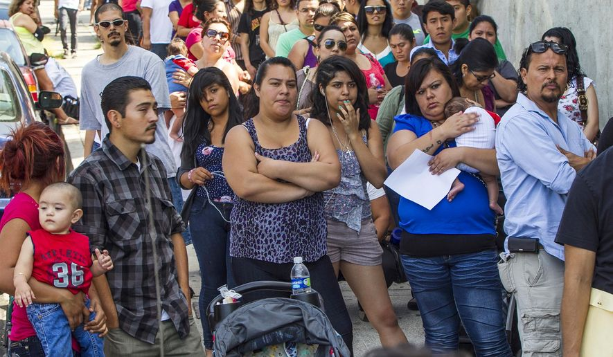 FILE - In this Aug. 15, 2012, file photo, a line of people living in the U.S. without legal permission wait outside the Coalition for Humane Immigrant Rights in Los Angeles. According to figures released in late June, 2015, by the U.S. Census Bureau, Hispanic Californians began to narrowly outnumber white Californians sometime in the first half of 2014. (AP Photo/Damian Dovarganes, File)