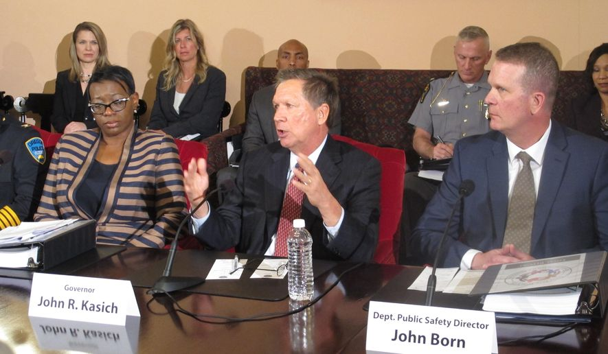 FILE - In this April 29, 2015, file photo, Ohio Gov. John Kasich, center, announces a plan for first-ever statewide police standards for the proper use of force, recruiting and hiring in Columbus, Ohio. Former state Sen. Nina Turner, left, and state public safety director John Born, right, both played roles in the standards' creation. The board, created by Kasich in April, meets for the first time Wednesday, July 8. (AP Photo/Andrew Welsh-Huggins, File)