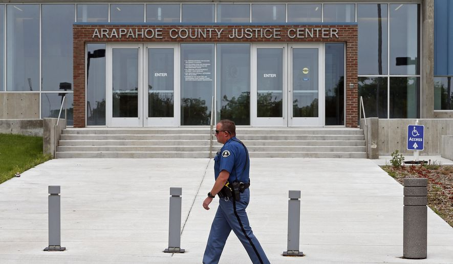 A sheriff's deputy walks the grounds of the Arapahoe County District Court, where the trial of Aurora movie theater shooter, James Holmes, continues, Wednesday, July 8, 2015, in Centennial, Colo. Prosecutors are tearing into the testimony of a second defense expert who concluded the shooter was so mentally ill that he couldn't tell right from wrong when killed 12 people and injured 70 during a packed midnight movie premiere three years ago. (AP Photo/Brennan Linsley)