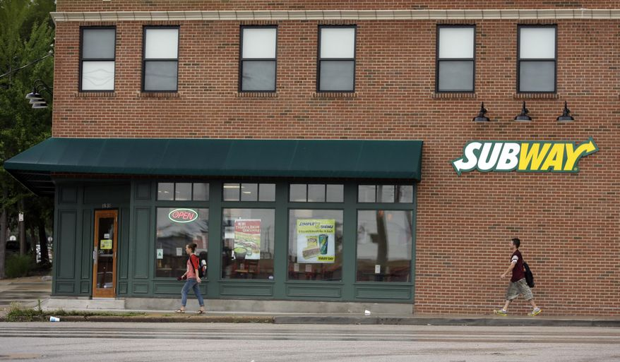 People walk past a Subway restaurant Tuesday, July 7, 2015, in St. Louis. FBI agents and Indiana State Police raided the home of Subway restaurant spokesman Jared Fogle on Tuesday, removing electronics from the property and searching the house with a police dog. (AP Photo/Jeff Roberson)