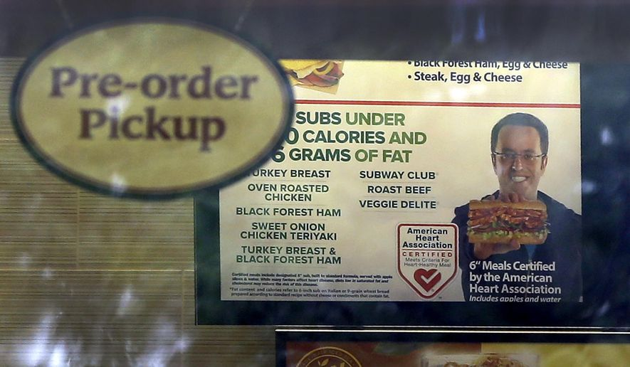 A photo of Subway restaurant spokesman Jared Fogle is seen on a menu board hanging inside one of its locations Tuesday, July 7, 2015, in St. Louis. FBI agents and Indiana State Police raided the home of Fogle on Tuesday, removing electronics from the property and searching the house with a police dog. (AP Photo/Jeff Roberson)