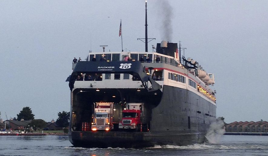 In this photo taken on Friday, July 3, 2015, the SS Badger docks in Ludington, Mich., to unload passengers and vehicles that made a 4-hour trip from Manitowoc, Wisc. The U.S. 10 sign on the back indicates that it connects the highway between Michigan and Wisconsin. The American Association of State Highway and Transportation Officials says that the route traveled by the ferry will be officially designated as a continuance route of U.S. 10. (AP Photo/Roger Schneider)