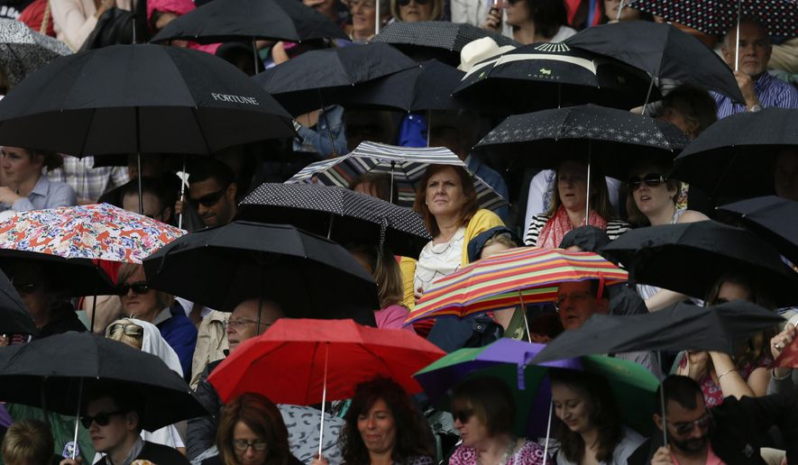 Spectators shelter under umbrellas as rain interrupts play on Court No. 1, during the men's quarterfinal singles match between Roger Federer of Switzerland and Gilles Simon of France,  at the All England Lawn Tennis Championships in Wimbledon, London, Wednesday July 8, 2015. (AP Photo/Pavel Golovkin)