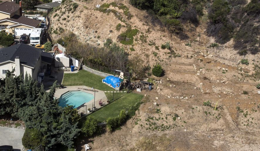 FILE - In this April 2, 2015, file photo, a home with a swimming pool sits near a dried out hillside in Altadena, Calif. The State Water Resources Control Board is hosting a workshop Wednesday, July 8, 2015,  to discuss how to encourage Californians to save by hitting them in the wallet. Two-thirds of water districts use some form of tiered water pricing.  (AP Photo/Ringo H.W. Chiu, File)