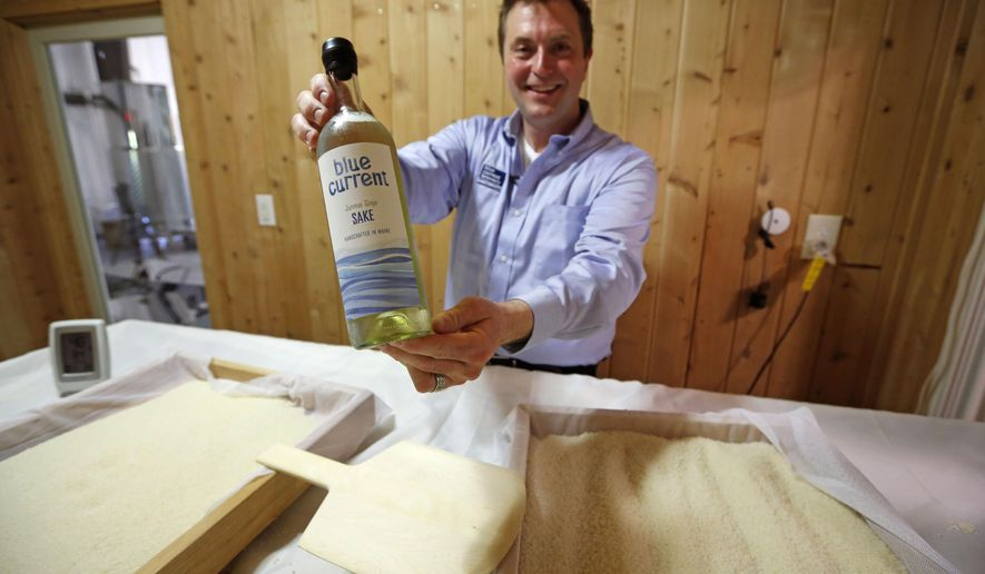 """In this photo taken, Friday, June 12, 2015, Dan Ford, founder of the Blue Current Brewery, poses with a bottle of sake at the brewery in Kittery, Maine. Steamed rice is inoculated in a sauna-like koji room for two days as part of the six week brewing process to make """"rice wine."""" (AP Photo/Robert F. Bukaty)"""