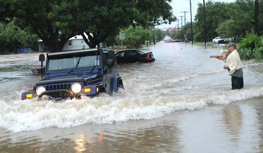 A homeowner throws a rock at a motorist driving through deep water on South 11th Street near Catclaw Creek, as the waves are lapping into the man's garage nearby Tuesday, July 7, 2015, in Abilene, Texas. (Nellie Doneva/The Abilene Reporter-News via AP) MANDATORY CREDIT