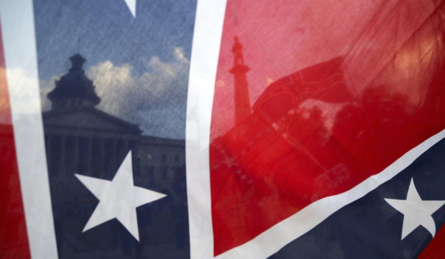 The South Carolina State House is seen through a Confederate flag held along Gervais Street, Monday, July 6, 2015, in Columbia, S.C. (Gerry Melendez/The State via AP)